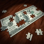 A puzzle in the shape of a dollar bill on a wooden surface, representing how to save money while moving.