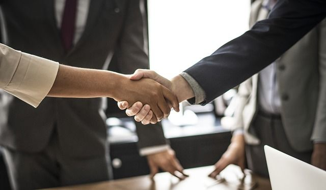 Two people shaking hands at a business meeting.