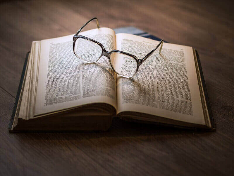A book and a pair of glasses on top of it.