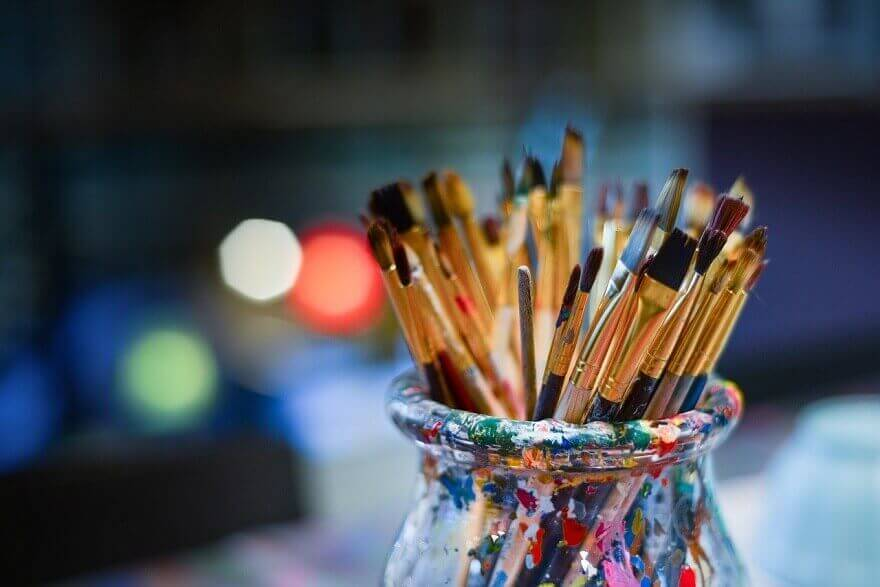 Many paintbrushes in a jar