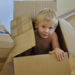 a boy sitting in a cardboard box; playing while moving with a newborn