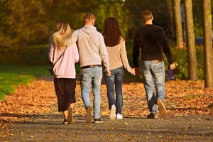 Two couples walking in the park.