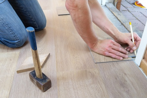 A person holding a pencil and measuring their floor using some home renovation tips.