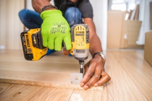 A person using an impact driver on a brown board trying to realize one of their home renovation tips.