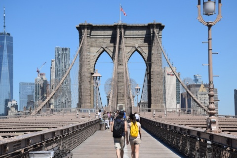 A couple on the Brooklyn Bridge preparing to explore some of the most interesting neighborhoods in Brooklyn.