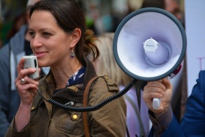A woman speaking with a megaphone at the protest.