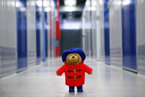 A teddy bear in the hal of a storage warehouse.