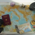 A map of the world, camera, passport, and a pair of flipflops.