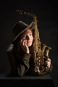 Woman posing with a saxophone.