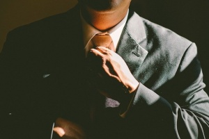 A man dressing a business suit and preparing for business