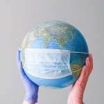 A woman holding a globe with rubber gloves and a mask over the globe.