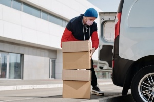 A man packing a pile of cardboard boxes into a van.