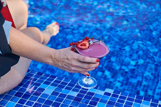 A woman drinking a coctail while enjoying the pool.
