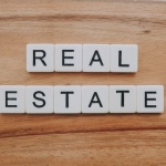 """Real estate"" written with scrabble letters on a wooden surface signifying Overland Park real estate trends."