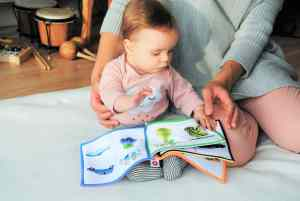A baby playing with a textured book
