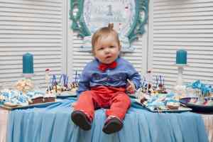 A baby boy sitting on the table surrounded with cupcakes for his 1st birthday
