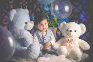 A boy sitting between two huge teddy bears