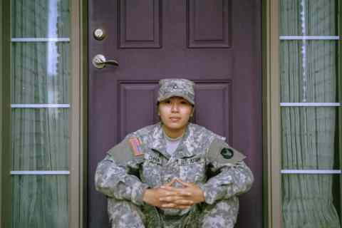 a female soldier sitting on the front step of her door to her home.