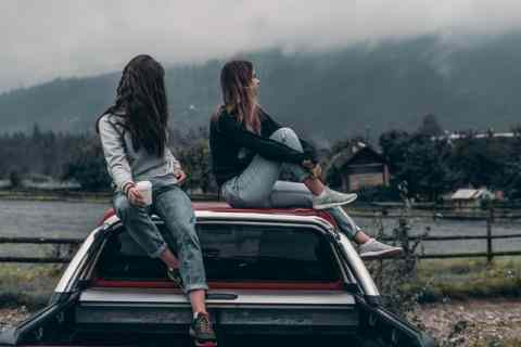 Two girls enjoying the view while sitting on top of a car.