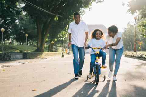 Parents teaching their daughter how to ride a bike.