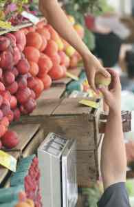 A person buying fruits at the market