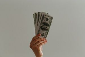 a hand holding dollar bills, read about should you rent or buy a house - New Hampshire edition