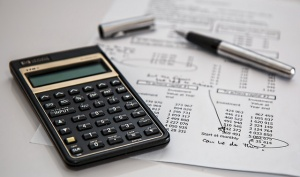 A calculator and list of expenses on paper